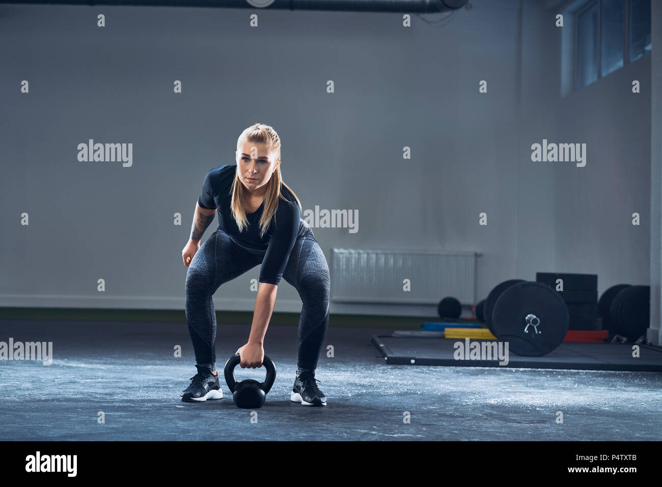 Woman exercising with kettlebell at gym - Stock Image