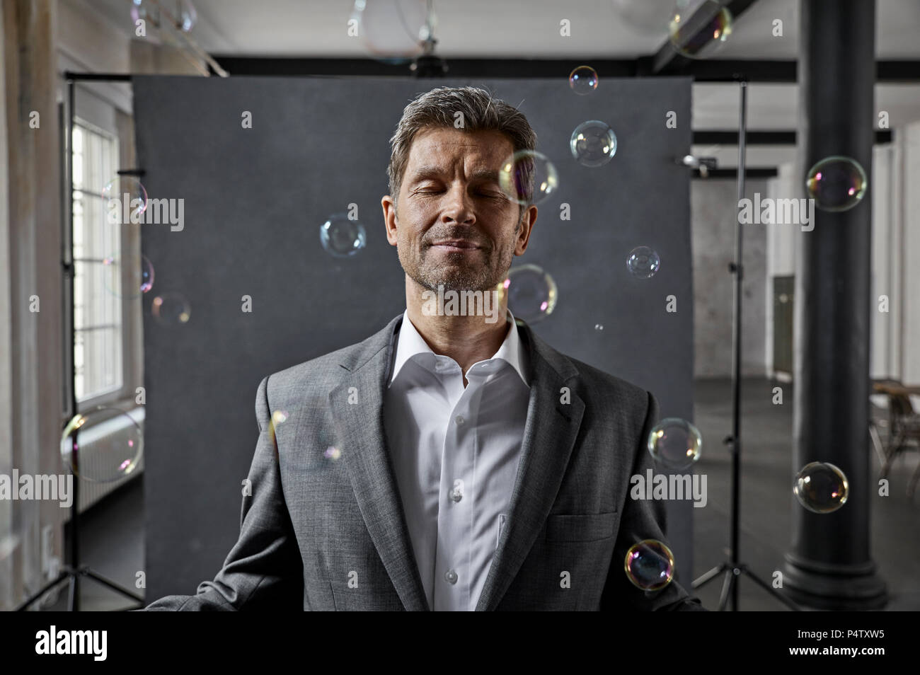 Portrait of mature businessman with bubbles in front of black backdrop in loft - Stock Image