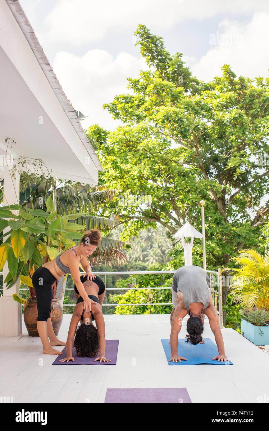 Yoga instructor teaching woman correct yoga pose on terrace - Stock Image