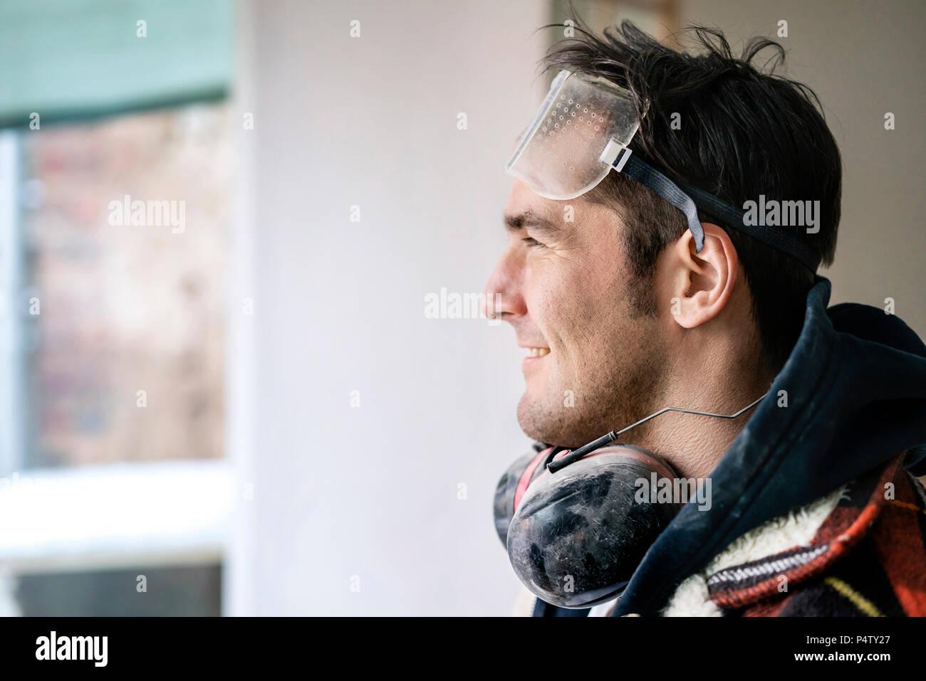 Portrait of a handyman , renovating flat, looking through window - Stock Image