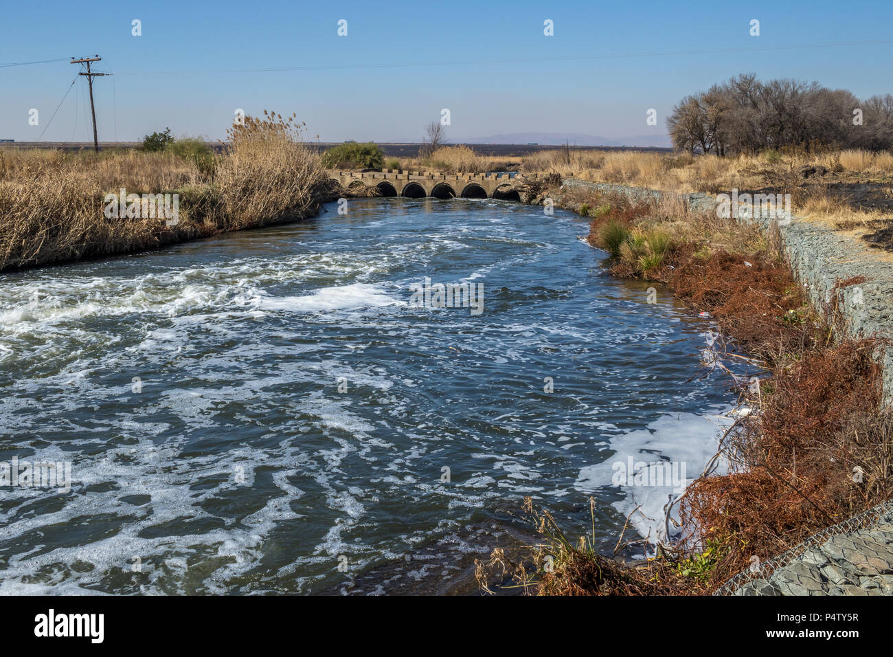Old concrete low water bridge with a modern gabion retaining wall to control erosion image with copy space in landscape format - Stock Image