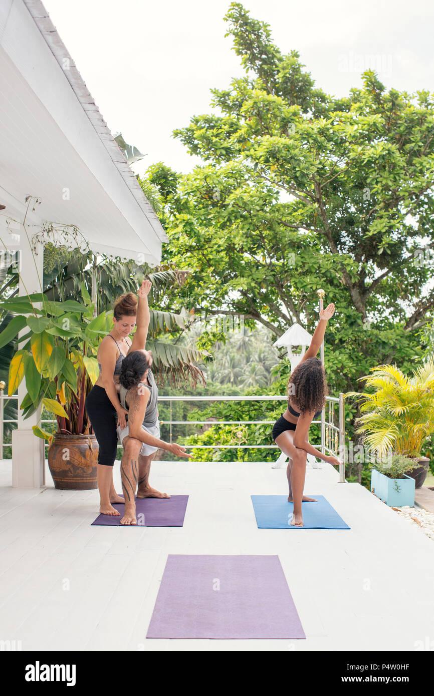 Yoga instructor teaching man correct yoga pose on terrace - Stock Image