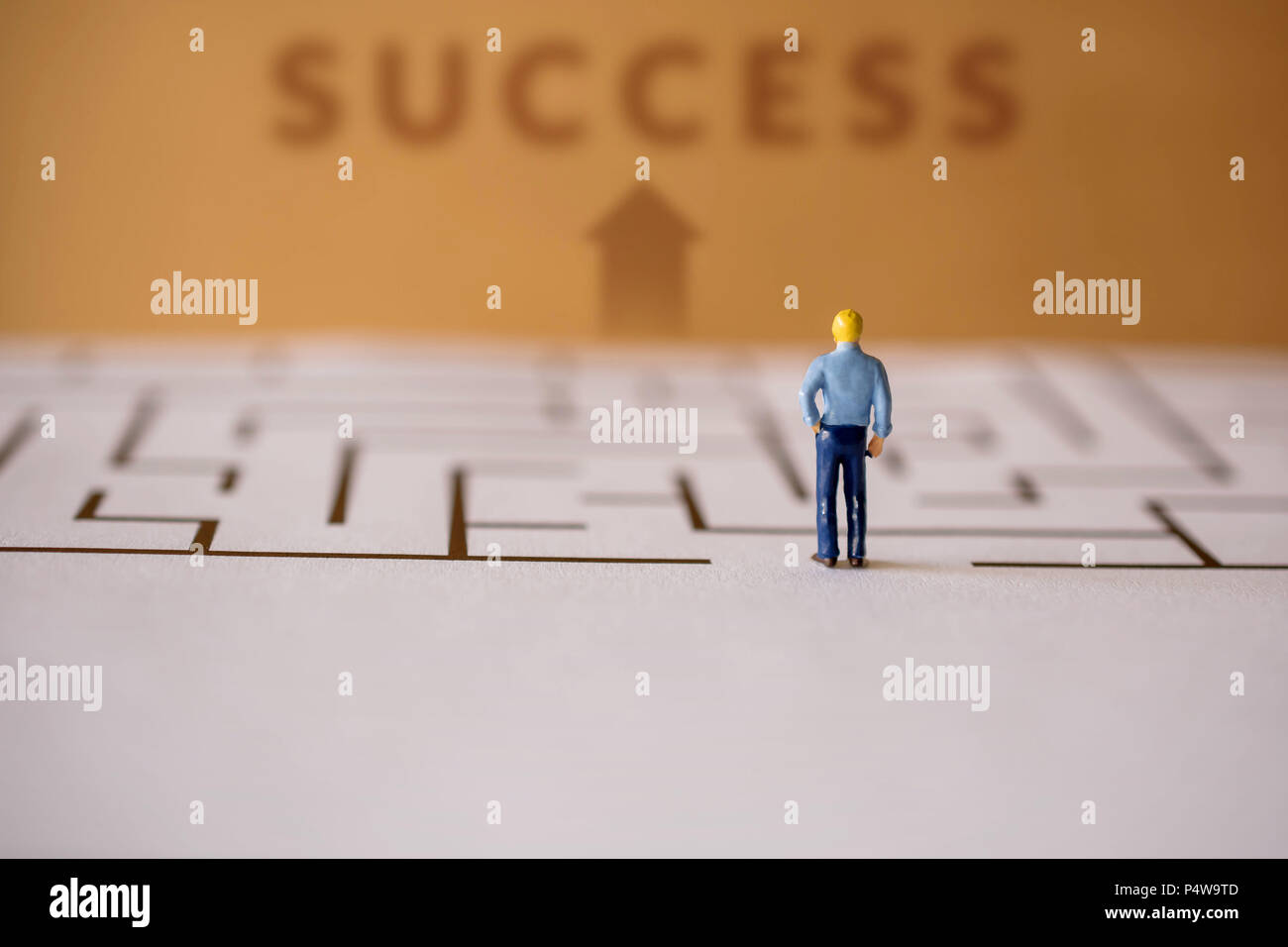 Challenge Concept. present by Miniature Figure of Businessman standing at Entrance of the Maze and Looking for Successful at the Finish Line - Stock Image