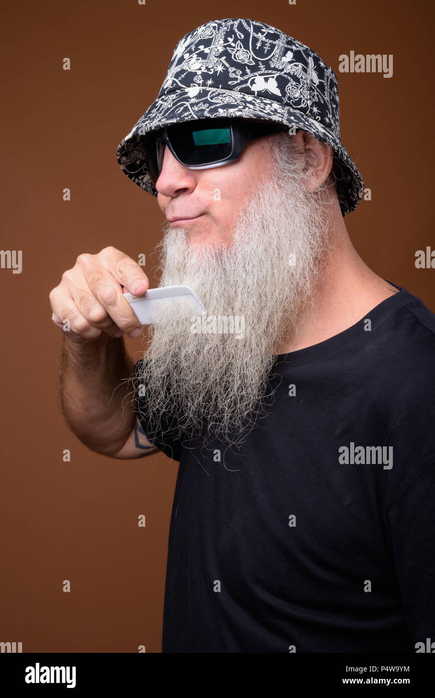 8209b5b39574 Mature man with long gray beard against brown background - Stock Image