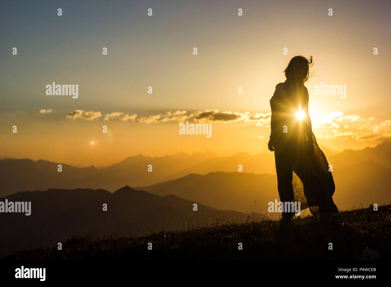 silhouete of girl in dress standing on grass in sunset mountains - Stock Image