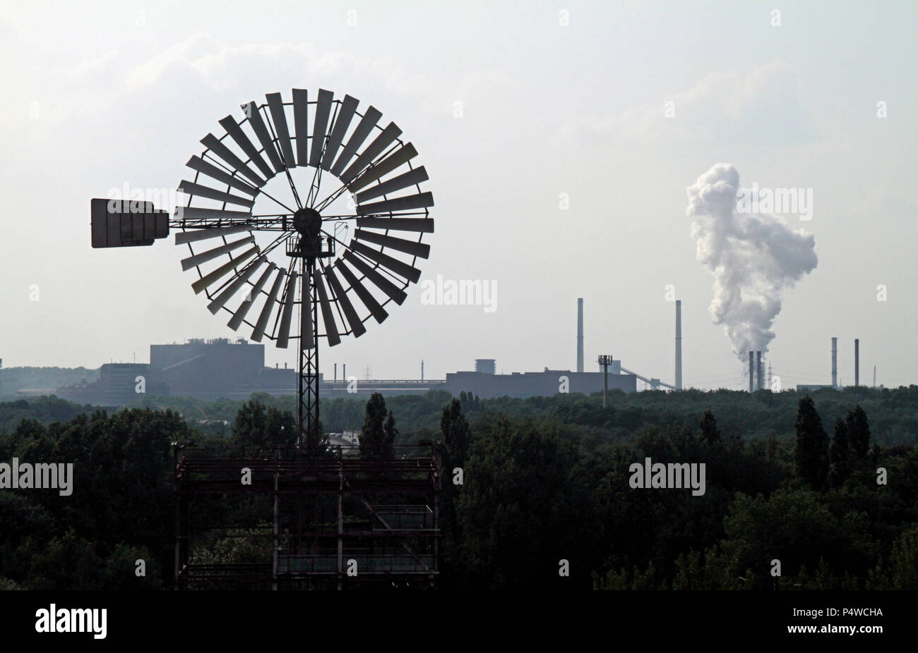 Windmill with factory in the background - Stock Image