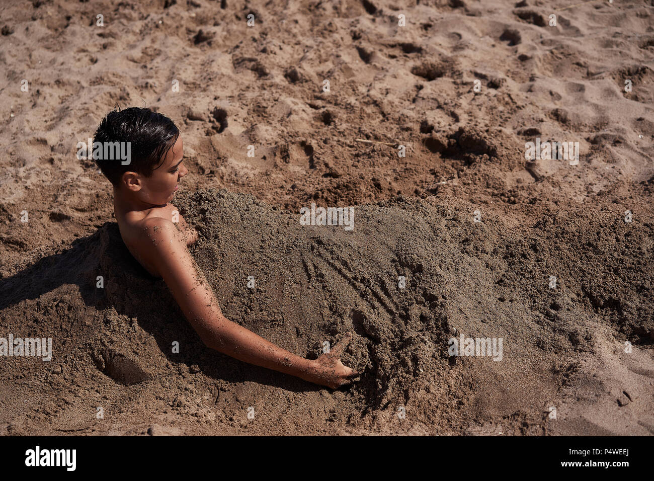 Boy buried in the sand beach - Stock Image