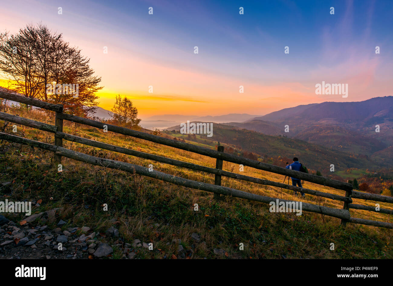 photographer on workshop at dawn in mountains. capturing gorgeous scenery of beautiful landscape with sun rising behind the forested mountain and fogg - Stock Image
