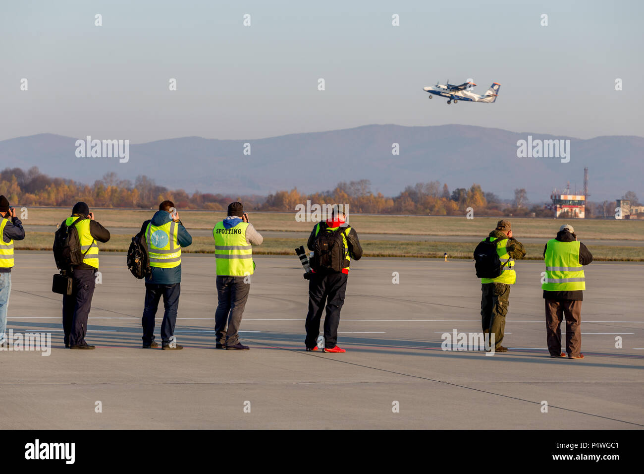 Russia, Vladivostok, 10/13/2017. Photographers make photos of plane taking off. DHC-6 of Aurora Airlines. Plane spotting, hobby, aviation. - Stock Image