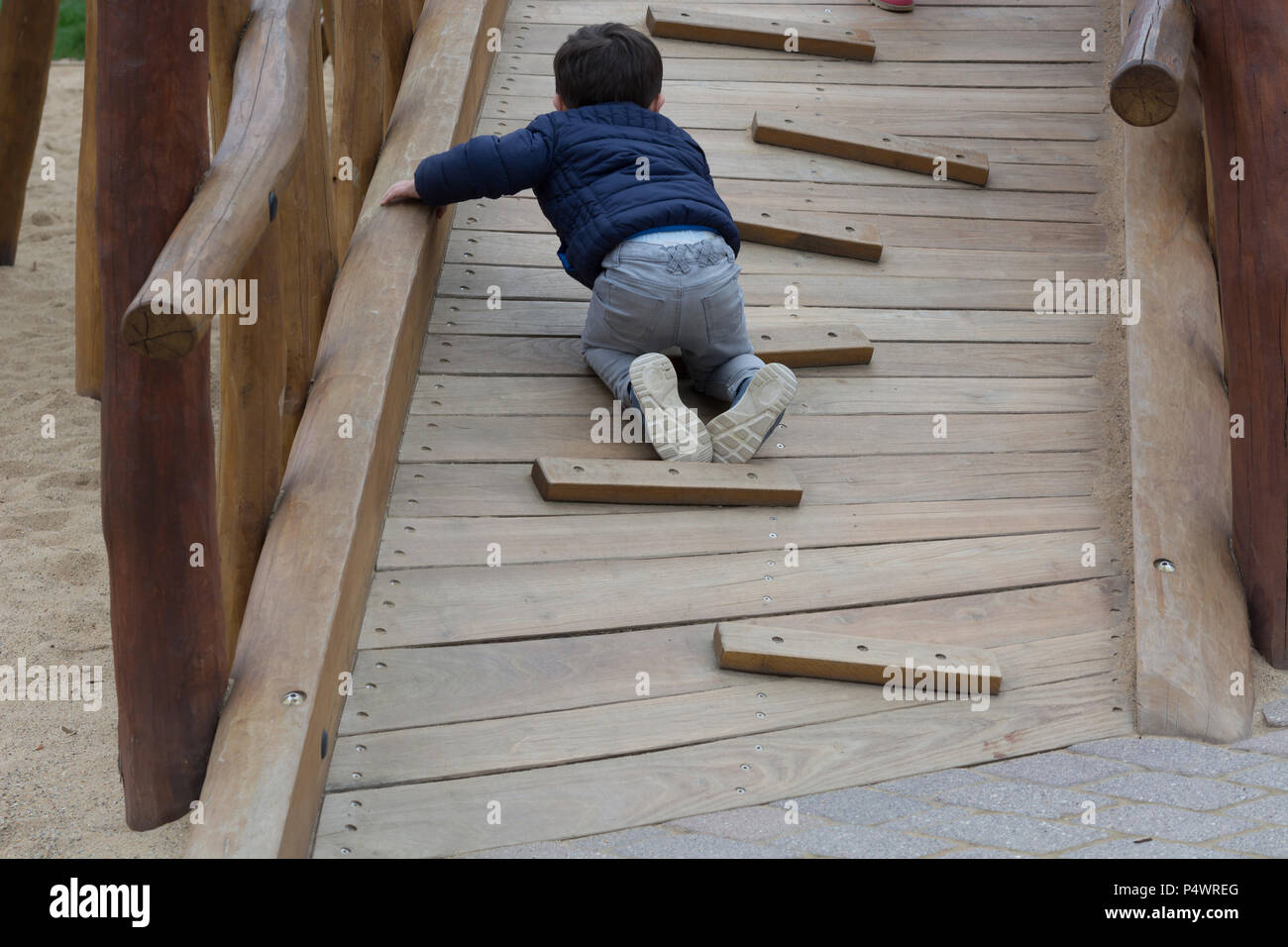 Happy young child having fun on a climbing frame outdoor - Stock Image
