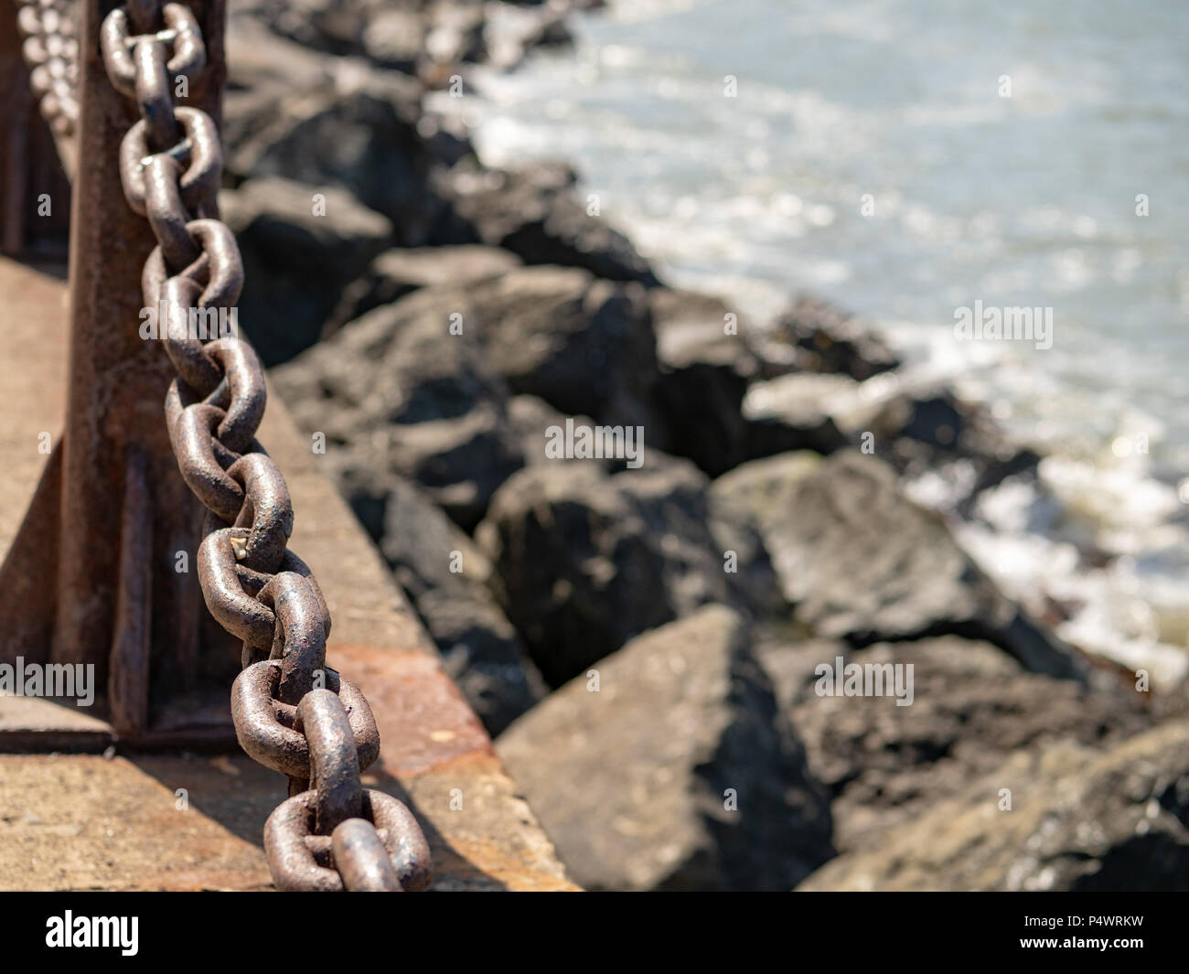 Sturdy, rusty chain blocking the sea with copy space to the right - Stock Image