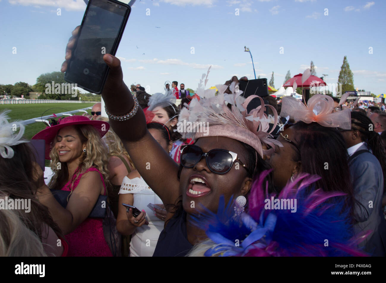 Rowdy crowds cheer on the horses at the side of the racetrack during Royal Ascot cup Stock Photo