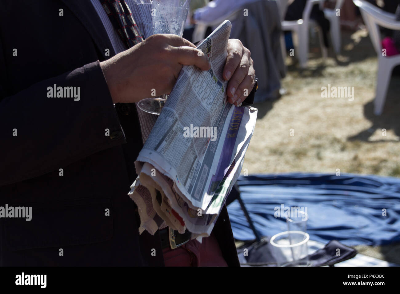 close up of man's hands holding the betting pages of the newspaper at the races Stock Photo