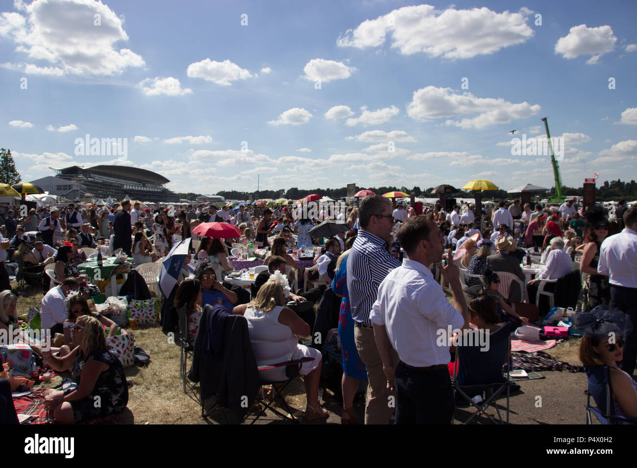 Large crowds of people sitting on grass in Windsor enclosure at Royal Ascot Stock Photo