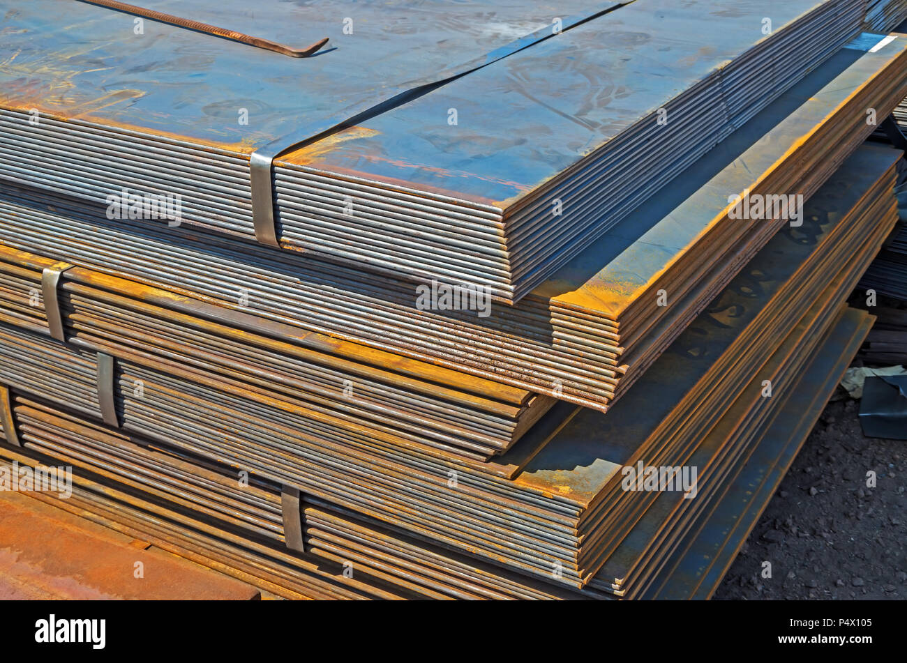 The rusty hot-rolled sheet metal in packs at the warehouse of metal products piled in the open air Stock Photo