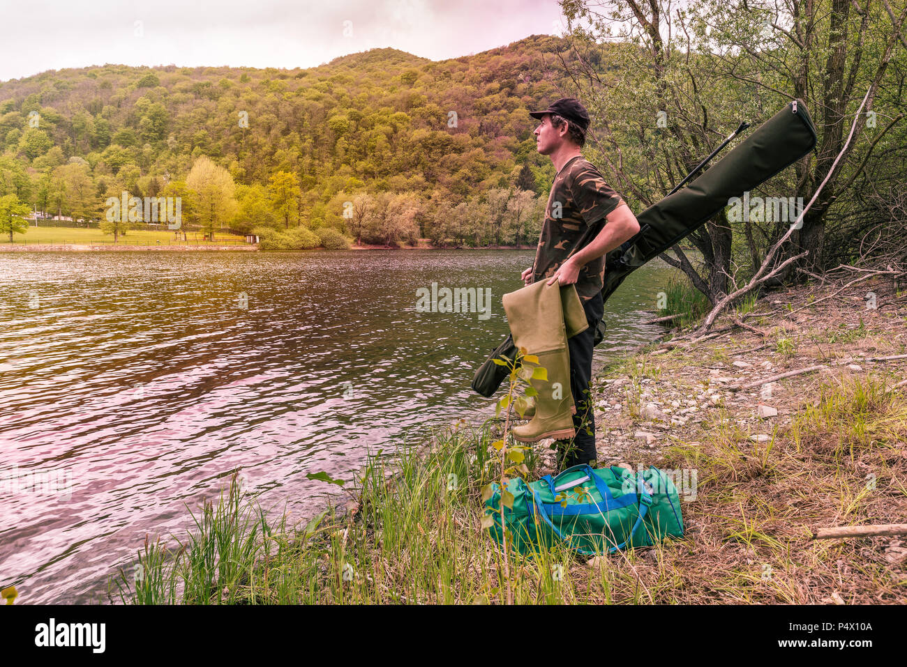 Fishing adventures, carp fishing. Fisherman on a lake shore with camouflage fishing gear, rubber boots, green bag and mimetic rod holdall - Stock Image