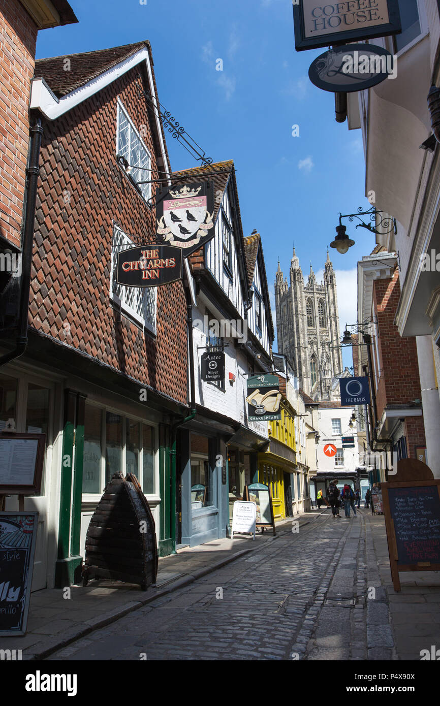 City of Canterbury, England. Shop and pub fronts on Canterbury's Butchery Lane, with Canterbury Cathedral's Bell Harry Tower in the background. - Stock Image