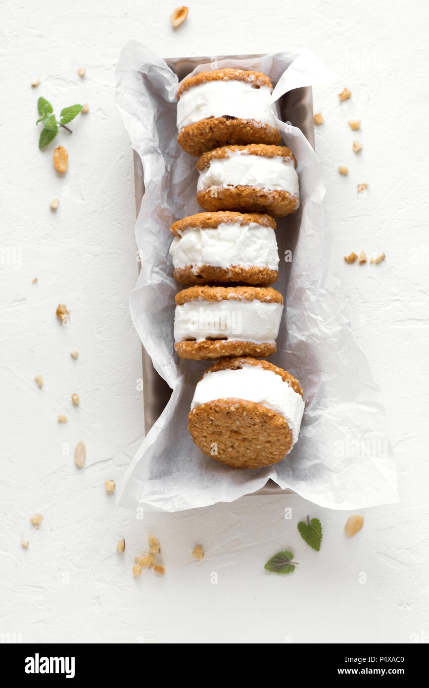 Ice cream sandwiches with nuts and wholegrain cookies. Homemade vanilla ice cream sandwiches on white background. - Stock Image