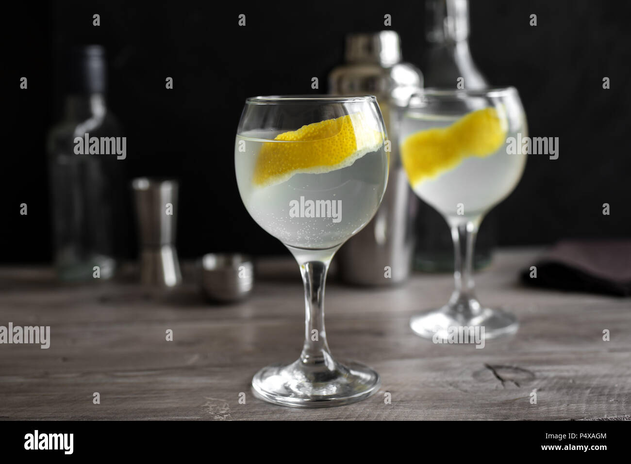 Gin fizz cocktail with lemon, cucumber, rosemary and ice. Gin tonic or gimlet on black background, copy space. - Stock Image