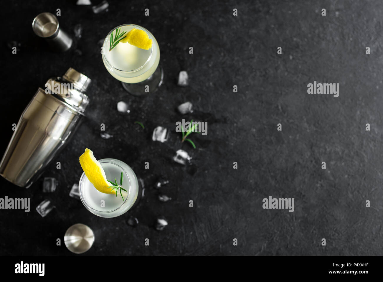 Alcohol Cocktail with lemon, rosemary and ice. Gin tonic fizz or gimlet cocktail on black background, copy space. - Stock Image
