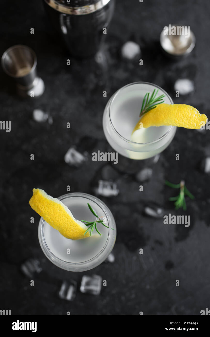 Alcohol Cocktail with lemon, rosemary and ice. Gin tonic fizz or gimlet on black background, copy space. - Stock Image