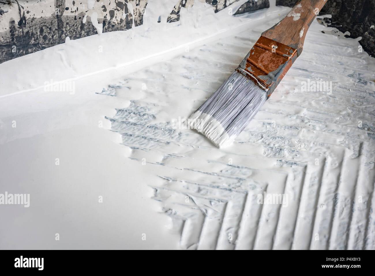 Wet Paint Brush In White Paint Stock Photo