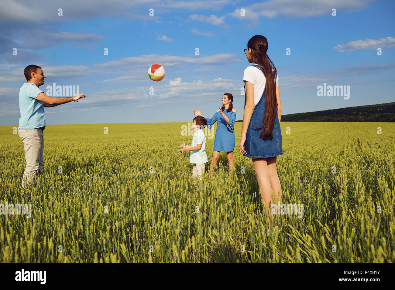 Happy family playing with ball in summer field - Stock Image
