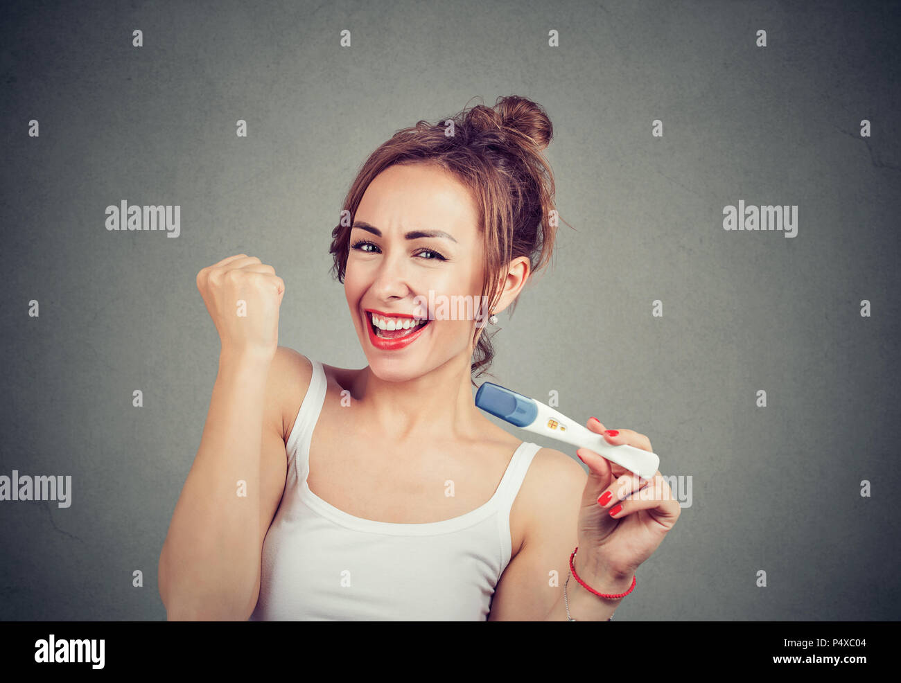 Happy young girl holding fits up and showing positive pregnancy test excited with great news on gray background - Stock Image