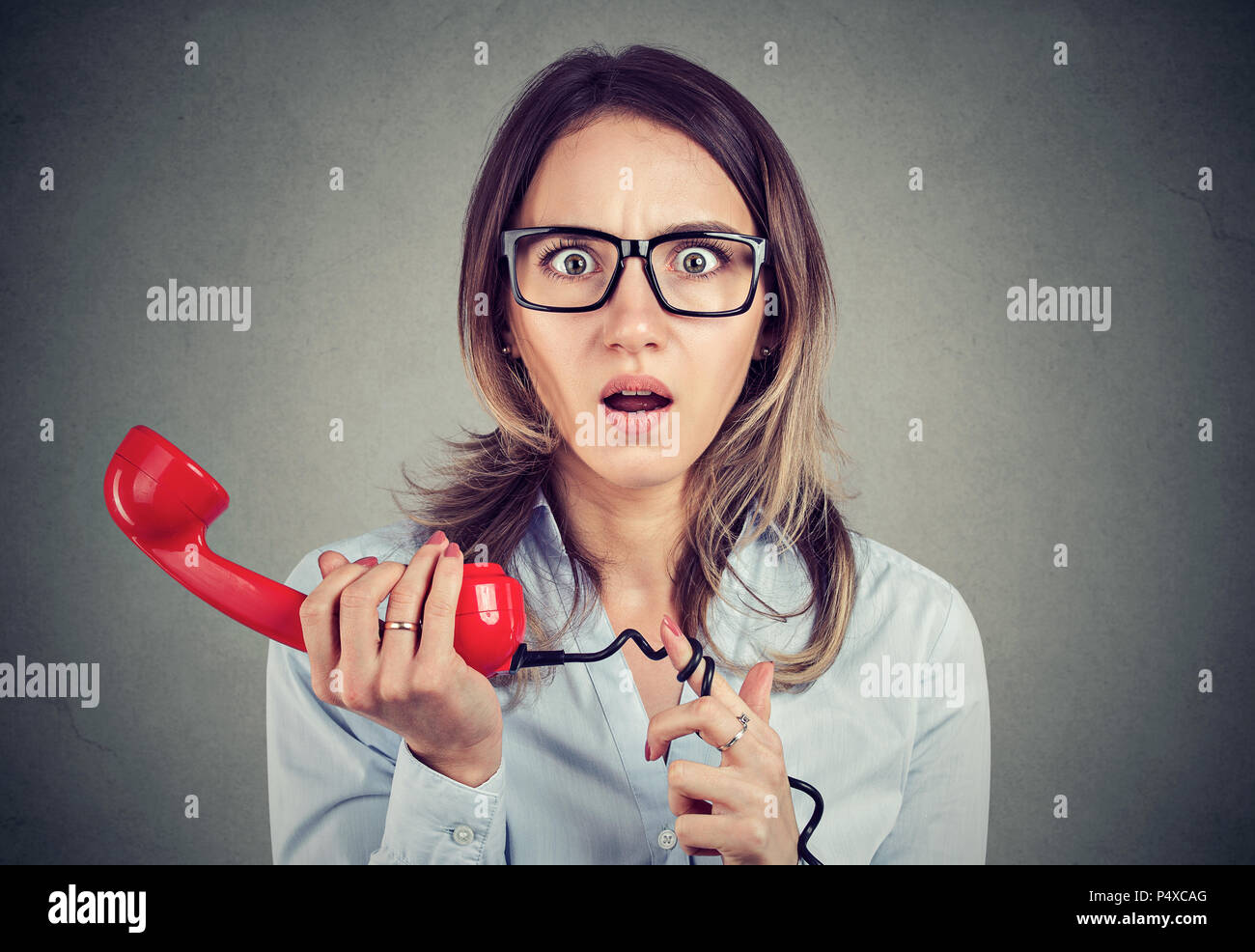Shocked young business woman receiving bad news over the telephone - Stock Image