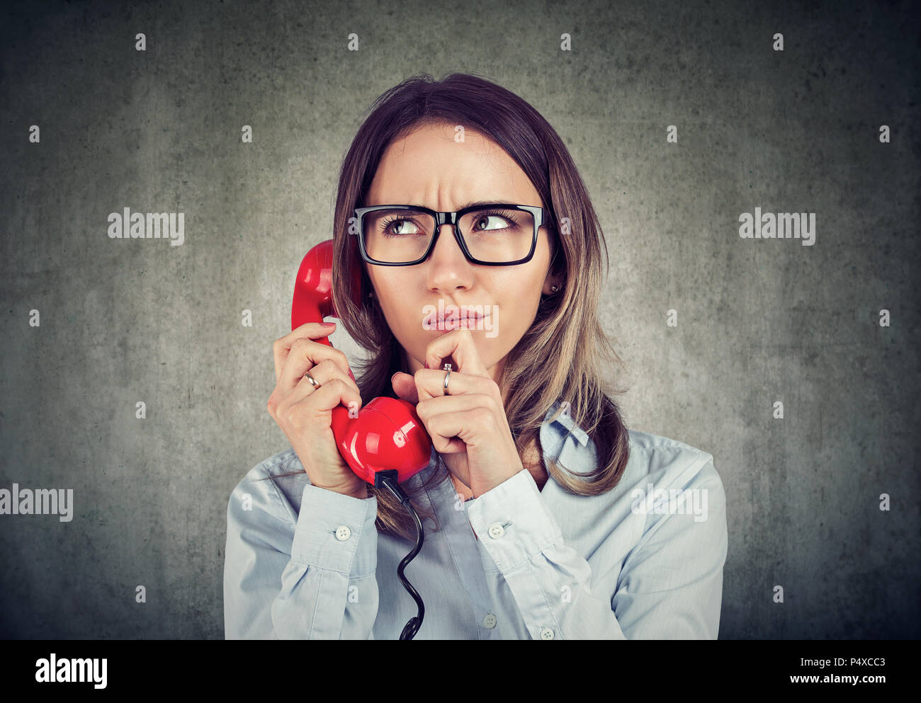Young woman in shirt and glasses having call on telephone and frowning with confusion being concerned with problems - Stock Image