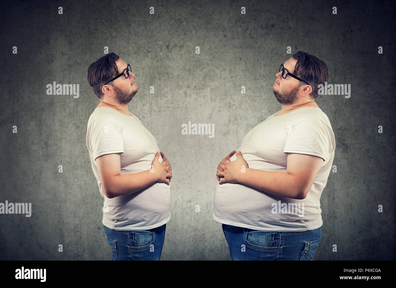 Young chubby man looking at fat himself feeling bloated. Diet and nutrition choice  healthy lifestyle concept - Stock Image