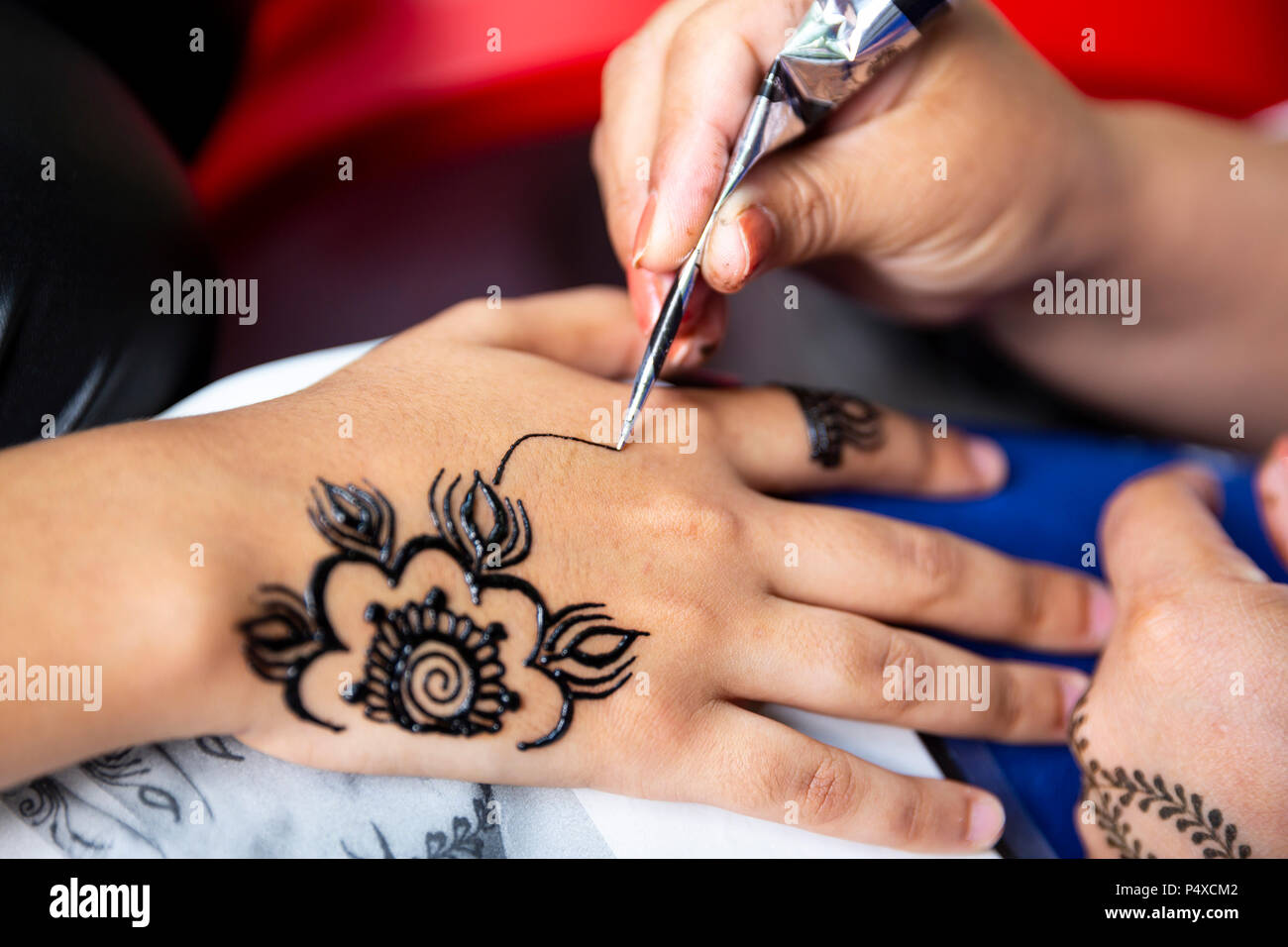 Woman painting black henna tattoo on a girl\'s hand Stock Photo ...