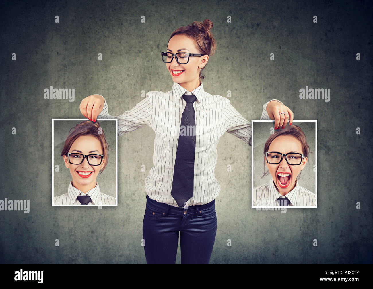Young cheerful woman in glasses holding pictures with good and bad emotions having mood swings and smiling at positive herself - Stock Image