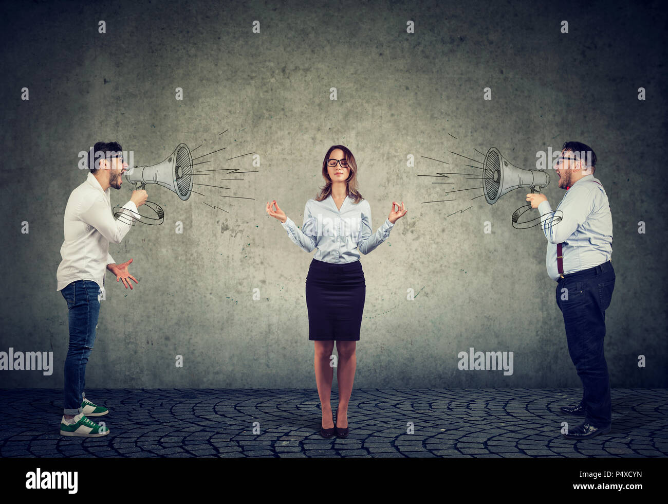 meditating young businesswoman paying no attention to two angry men screaming at her in megaphone - Stock Image