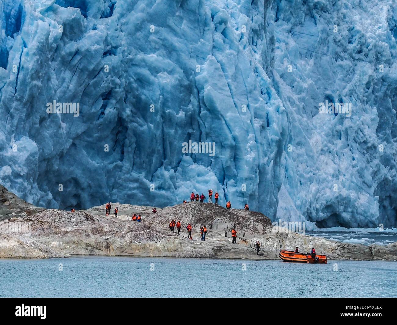 Tourists wearing life jackets explore a glacier in Torres del Paine National Park, Magallanes y de la Antartica, Patagonia, Chile Stock Photo