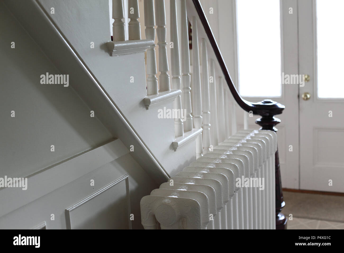Interior Of An Old House Showing Front Doors, Steam Radiator, Staircase  With Balusters And Hand Rail.
