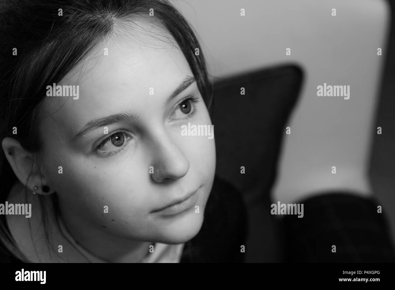 A portrait of a beautiful young woman looking up and away from the camera - Stock Image