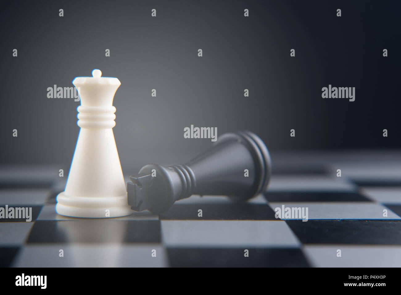 Chess set on chess board fallen black king on white queen women power concept selective and soft focus