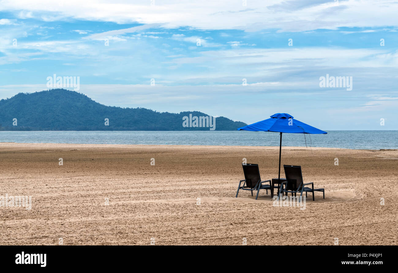 Sun loungers and a parasol on a totally empty beach of golden sand in Kota Kinabalu, Borneo, Malaysia - Stock Image