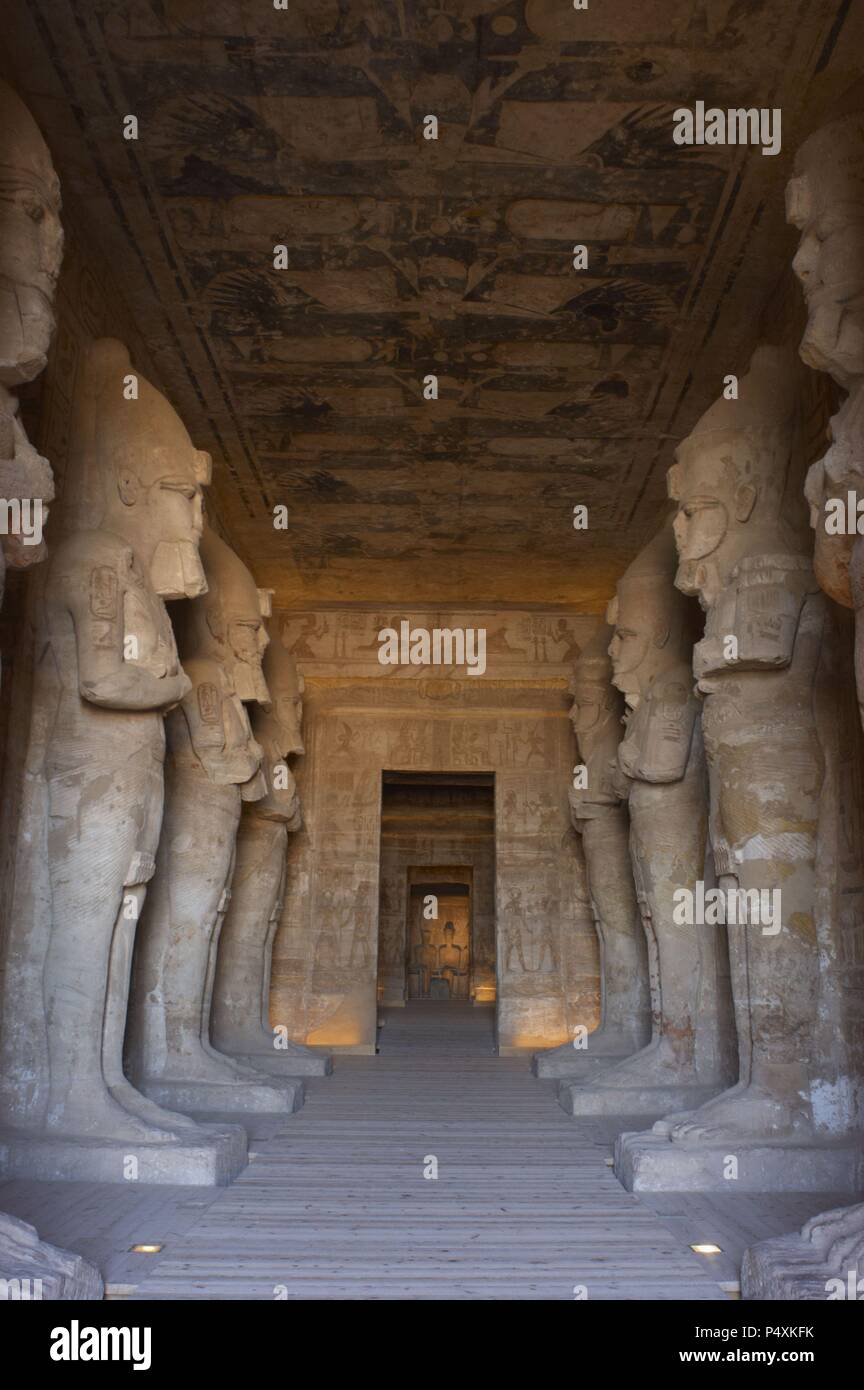 Egyptian art. Great Temple of Ramses II (1290-1224 BC). Funerary temple carved in the rock. View from inside the first room, with eight statues of Ramses II as the god Osiris. Abu Simbel. Egypt. Stock Photo