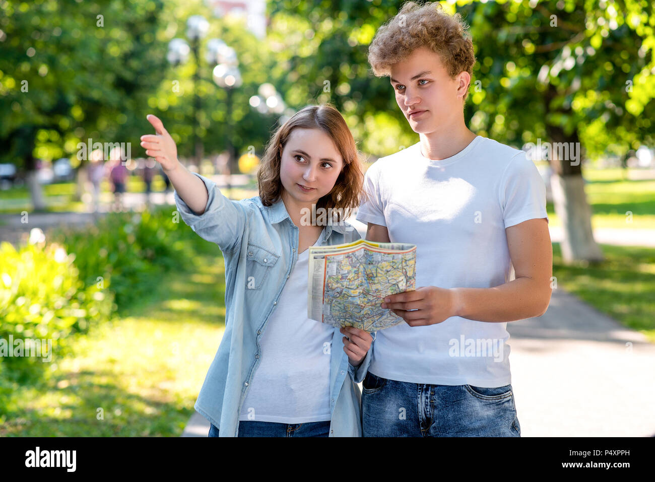 The girl shows the man direction of movement. Summer in nature. The passer-by shows where to go to the tourist. Young couple walking in the park in hands holding a road map. - Stock Image