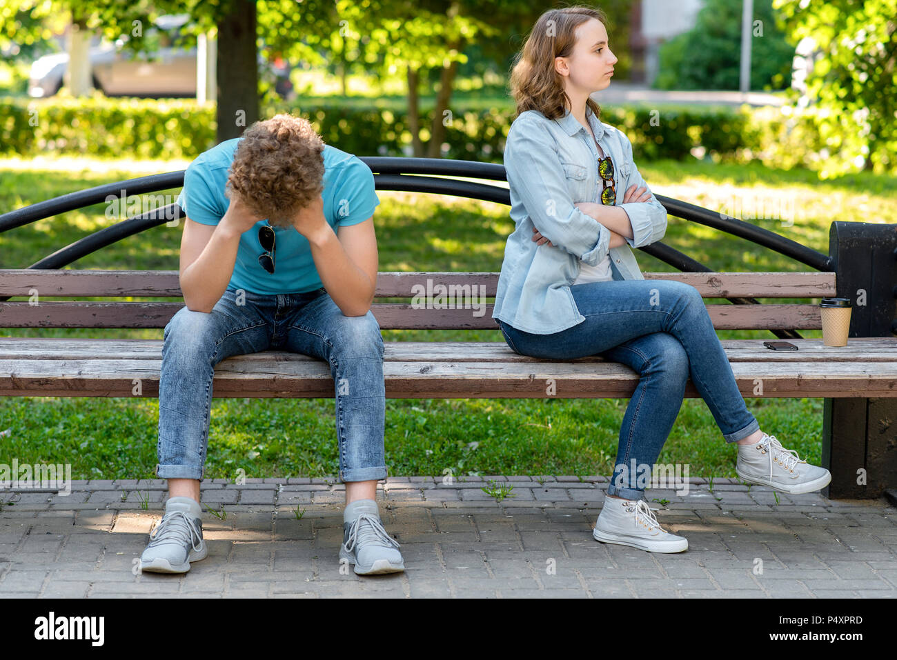 A guy with a girl is sitting on a park bench in summer. The concept is ruined by family life. Quarrels and misunderstandings in the relationship. The silence of the problem in family life. - Stock Image
