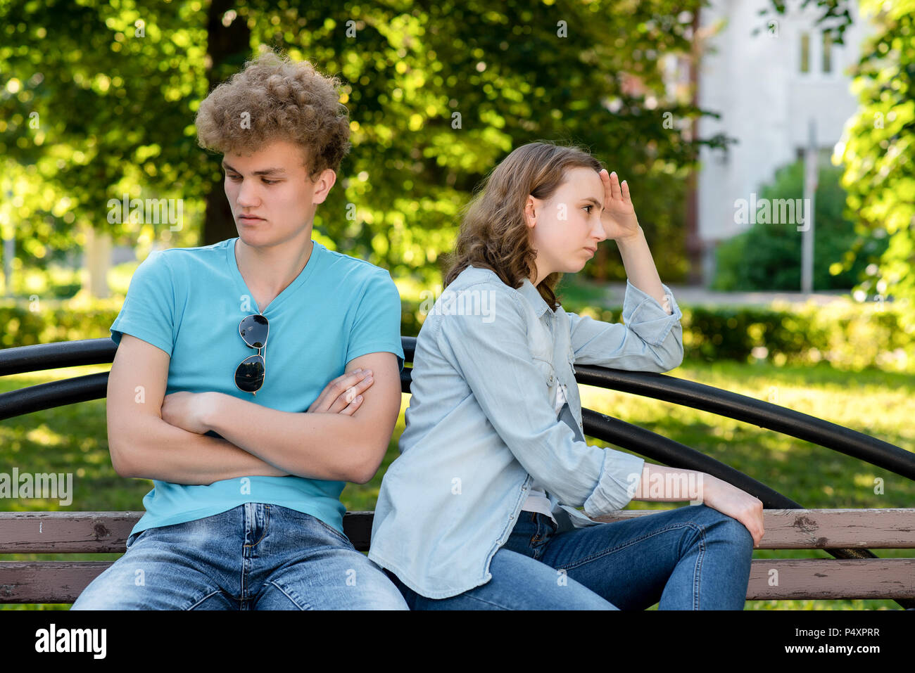 Young couple in summer in park outdoors. Problems in family life. The concept of misunderstanding is a mistrust of insults in a relationship. They sit on a bench in the city. - Stock Image