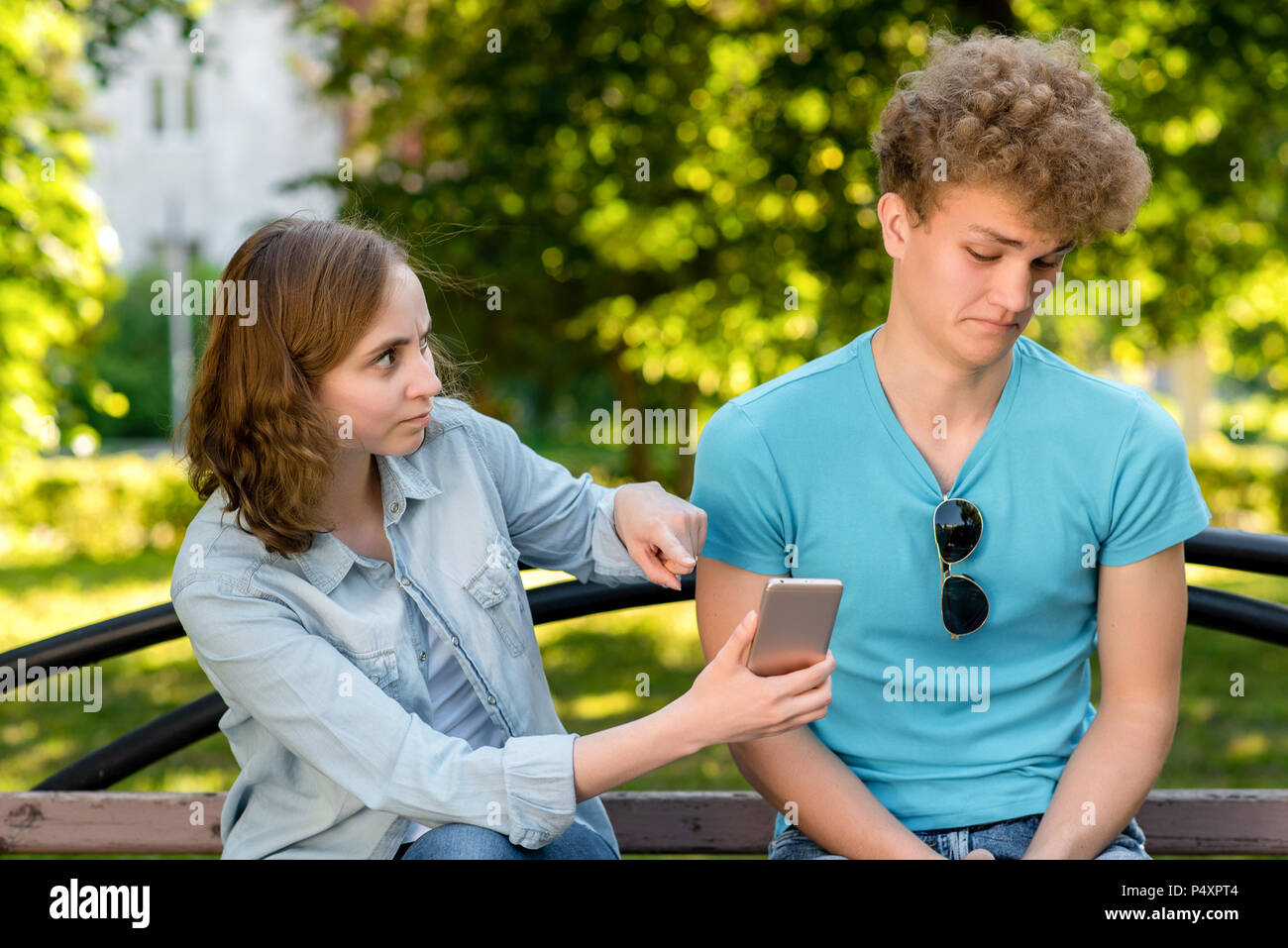 Guy with girl on nature. A woman is pointing at smartphone. Guy looks at correspondence with astonishment. Concept of betrayal betrayal of a young couple in summer. The problem is in relationship. - Stock Image