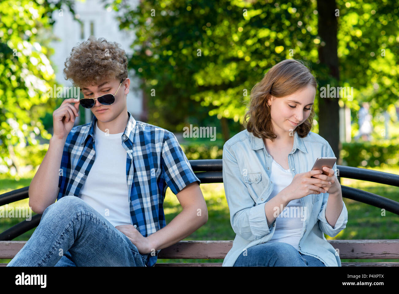 The guy and the girl are sitting on bench. Summer in nature. A girl in her hands holds a smartphone communicates in social networks. The guy spies Through glasses behind the girl. - Stock Image