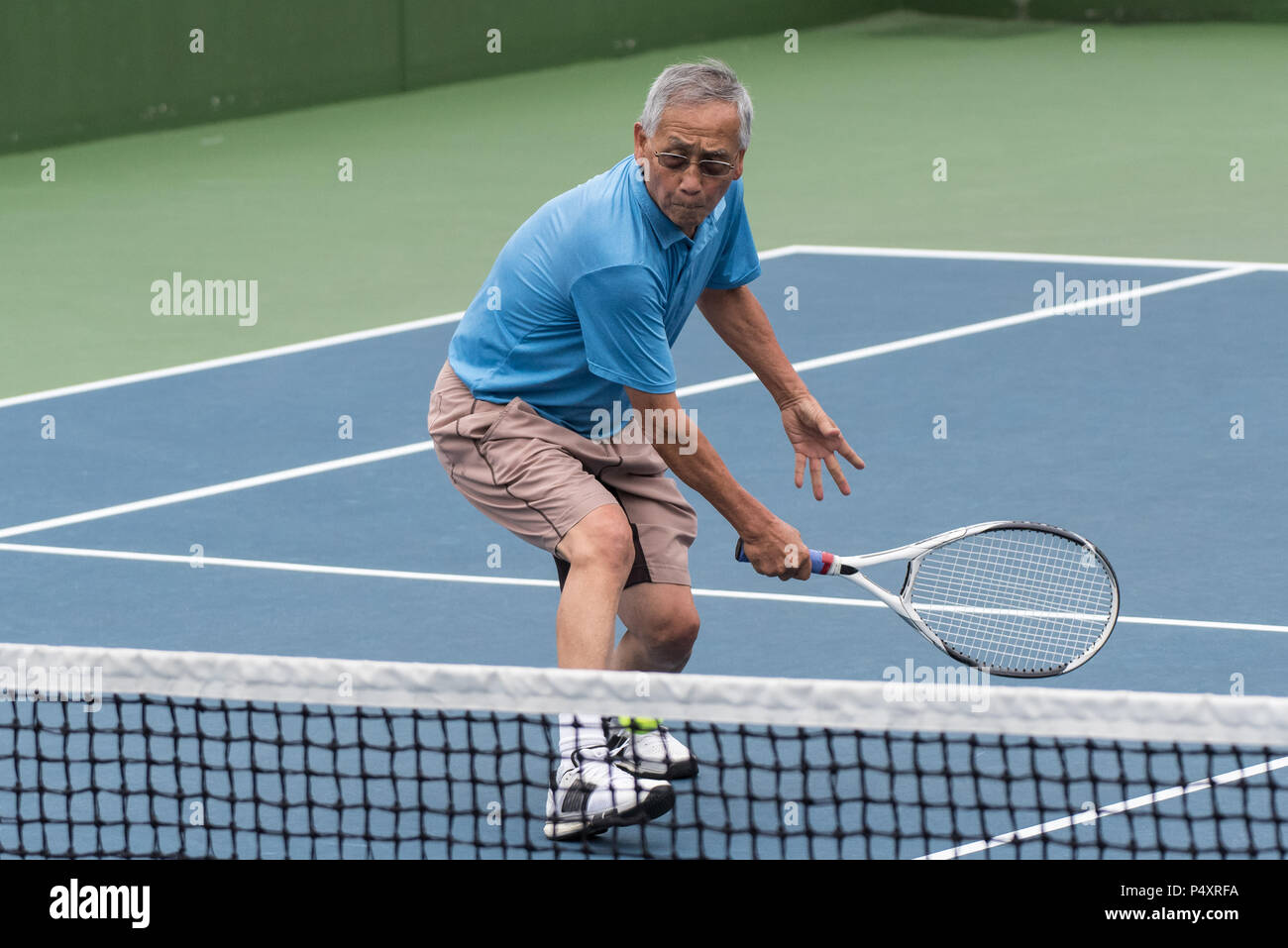 Healthy Chinese elderly man showing flexibility while reach for the low tennis backhand volley. - Stock Image