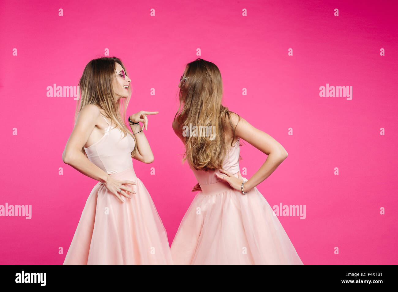 Quarrel of two sisters in pink dresses. - Stock Image