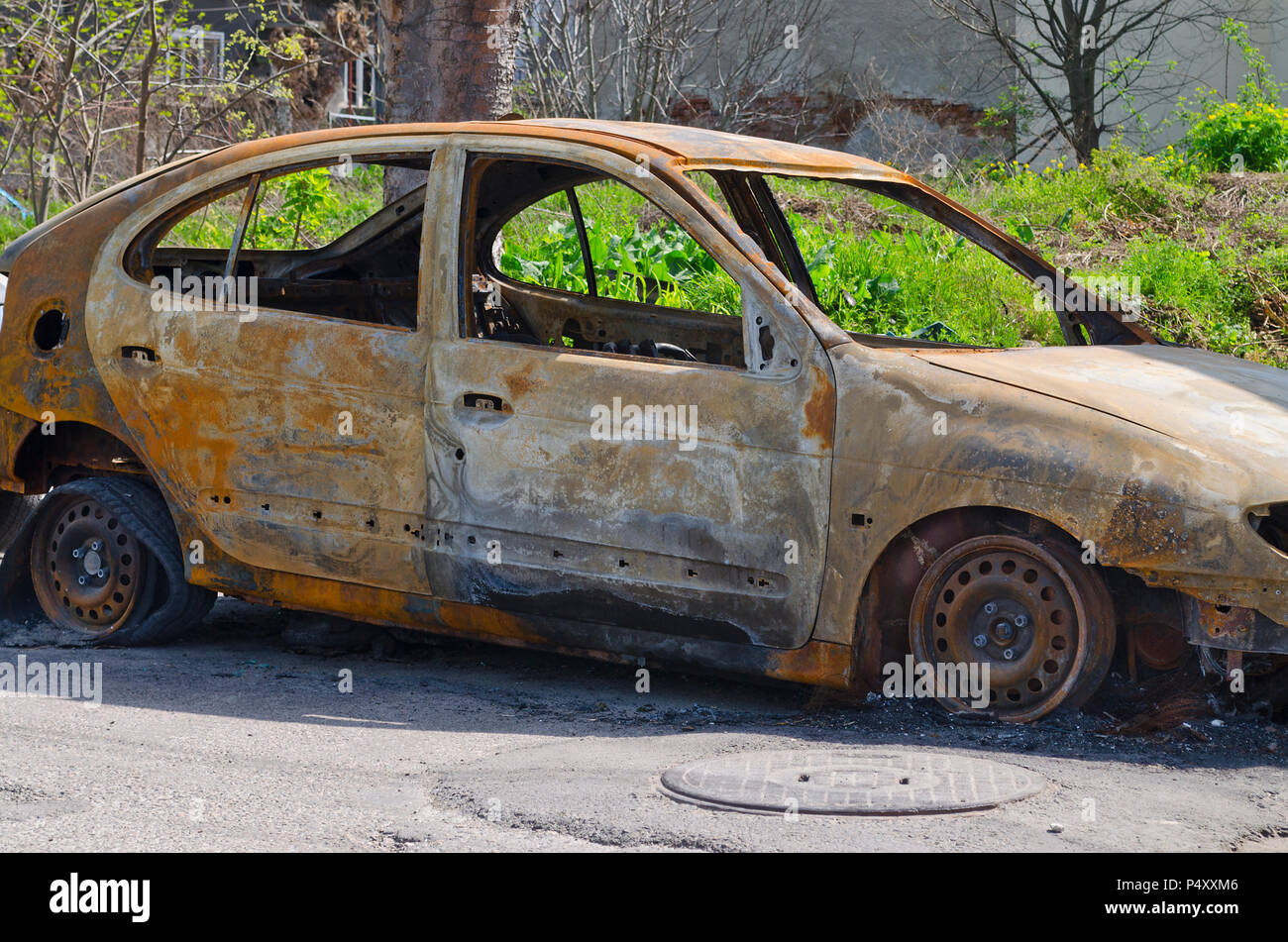 Burned car parked on the street side view - Close up photo of a burned out car - Stock Image