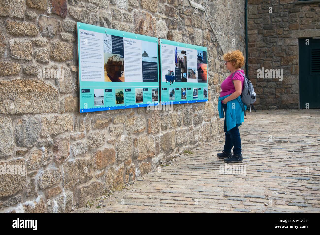A female tourist reading the interpretation at St. Michael's Mount, Cornwall, UK - John Gollop - Stock Image