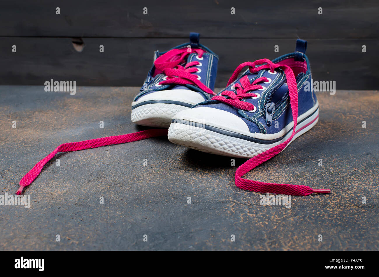 blue shoes with loose pink shoelaces
